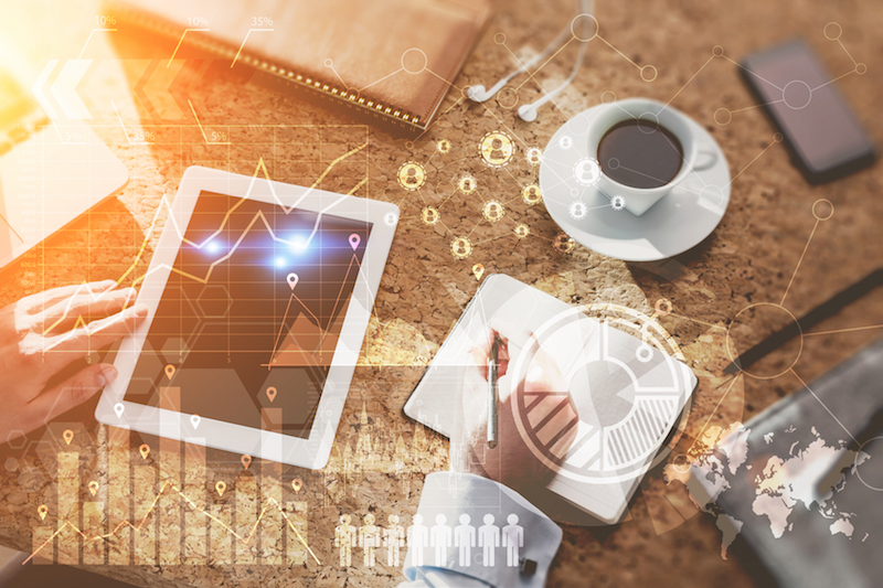 Top view of a man at his workplace in office. Tablet, smart phone and coffee on table. Graphs and schemes on foreground. Concept of office work. Elements of this image furnished by NASA. Toned image. Double exposure